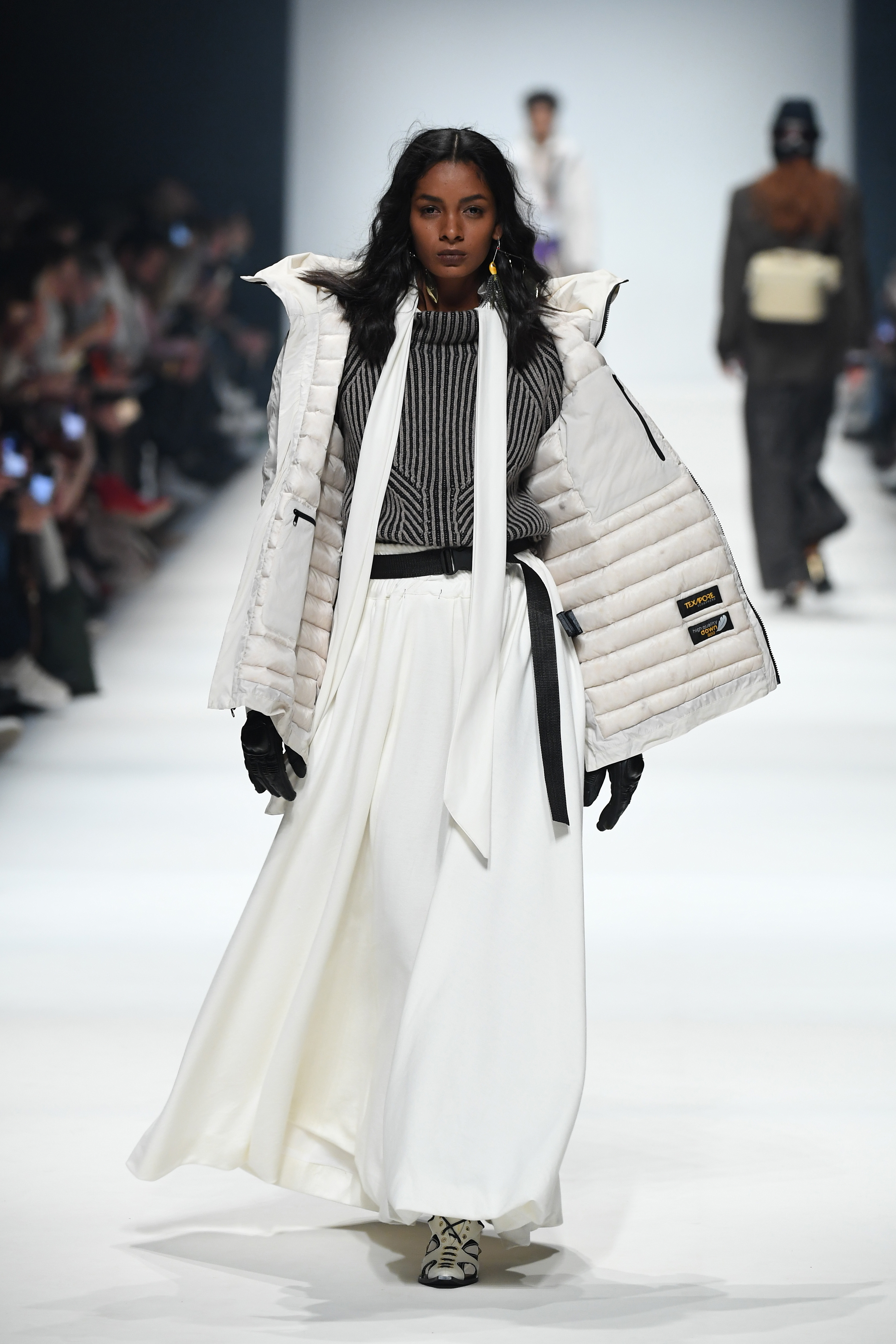 BERLIN, GERMANY - JANUARY 14: A model wearing a jacket by Wolfskin Tech Lab, shirt by Miomartha, pullover by Lanius, skirt by Hi On Life, gloves by Biker-Zone, socks by Swedish Stockings and shoes by Balluta walks the runway at the Neonyt show during Berlin Fashion Week Autumn/Winter 2020 at Kraftwerk Mitte on January 14, 2020 in Berlin, Germany. (Photo by John Phillips/Getty Images for MBFW)