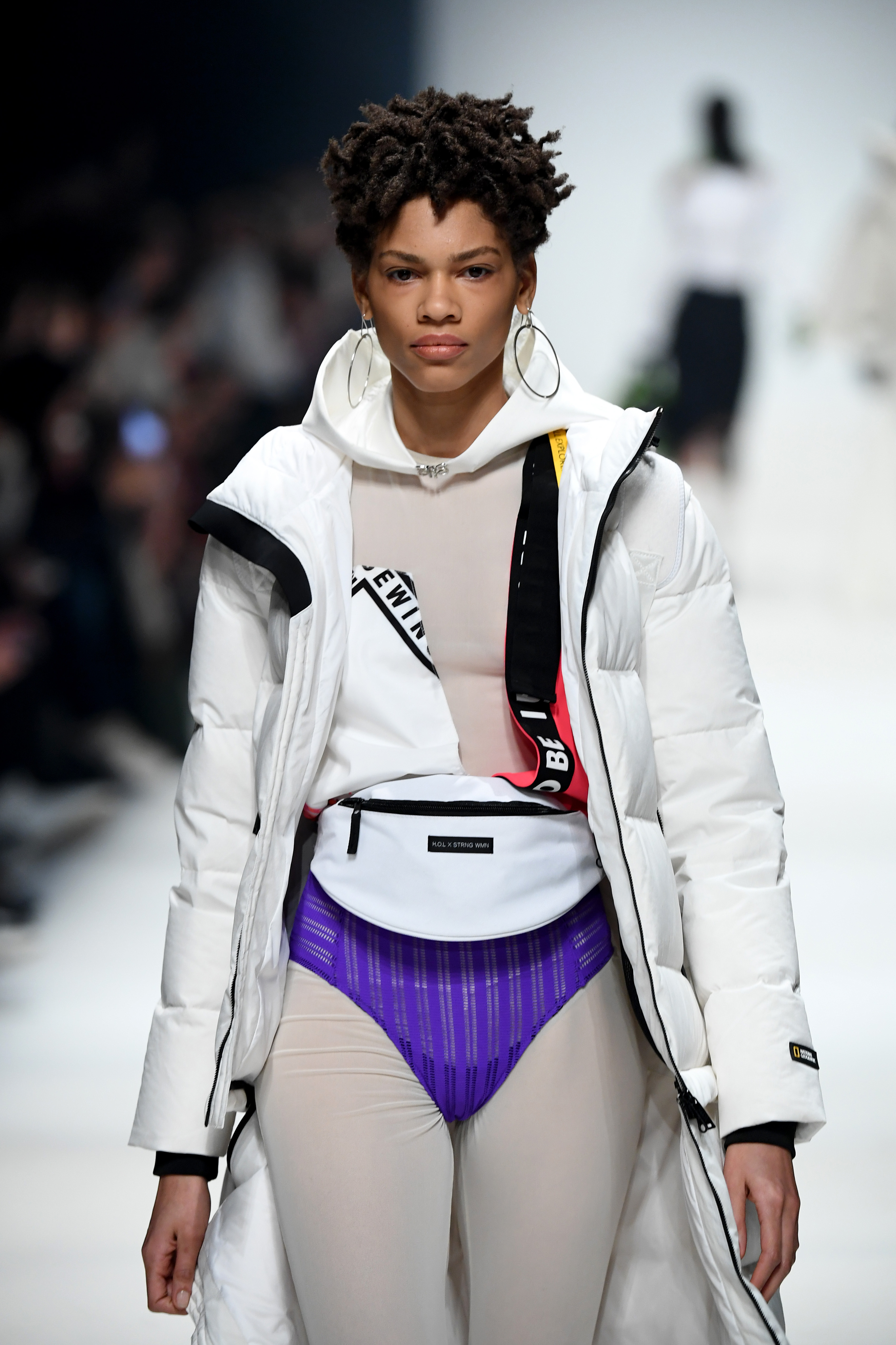 BERLIN, GERMANY - JANUARY 14: A model wearing a coat by National Geographic, jumpsuit by Gaya, lingerie by Opaak, earring & ring by Lani Lees, ring by Folkdays and a bag by Hi On Life walks the runway at the Neonyt show during Berlin Fashion Week Autumn/Winter 2020 at Kraftwerk Mitte on January 14, 2020 in Berlin, Germany. (Photo by John Phillips/Getty Images for MBFW)
