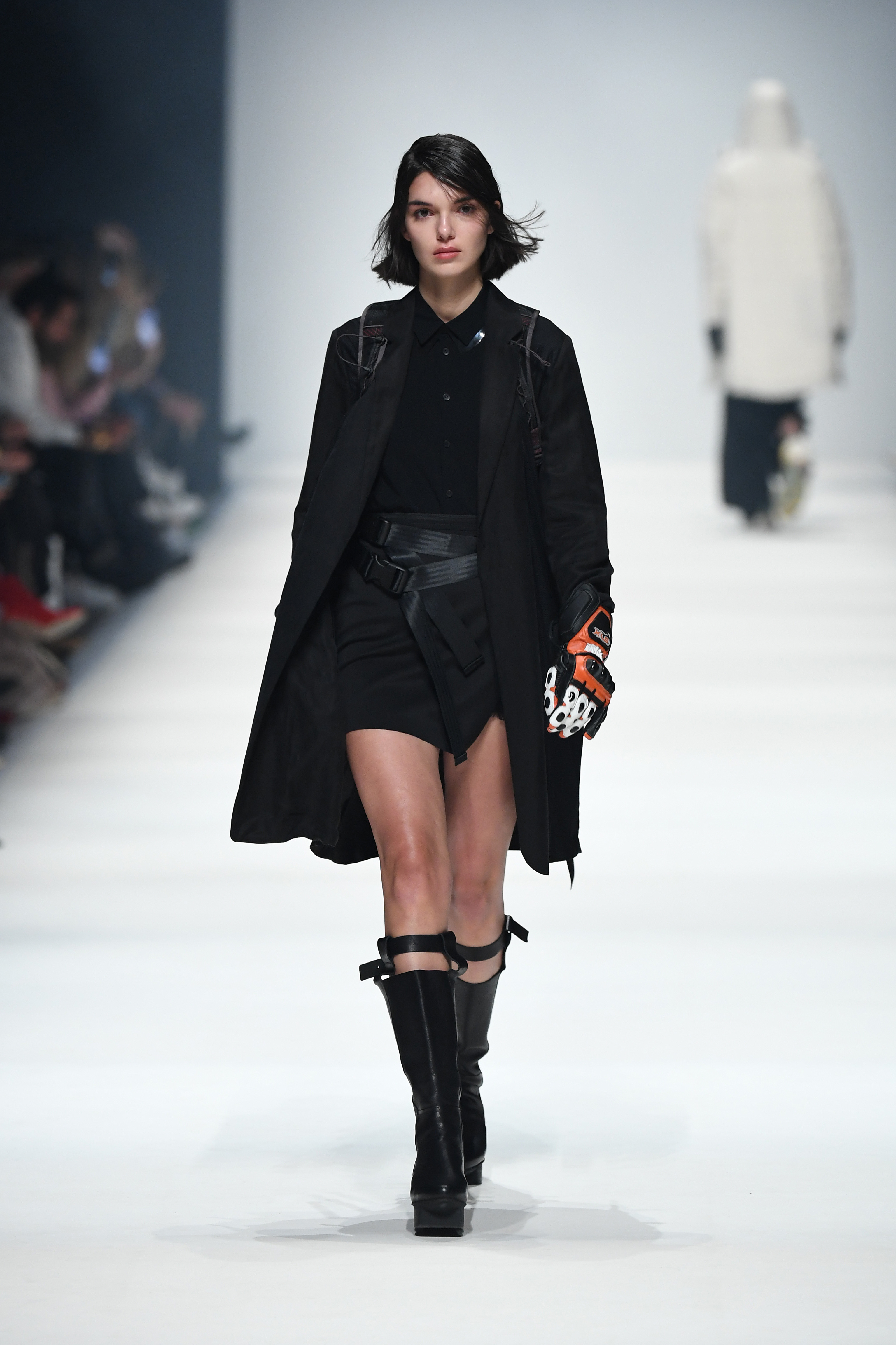 BERLIN, GERMANY - JANUARY 14: A model wearing a coat by People Berlin, blouse by Esther Perbandt, backpack by Klaettermusen, skirt by Nakt, gloves by Biker-Zone and shoes by Trippen walks the runway at the Neonyt show during Berlin Fashion Week Autumn/Winter 2020 at Kraftwerk Mitte on January 14, 2020 in Berlin, Germany. (Photo by John Phillips/Getty Images for MBFW)