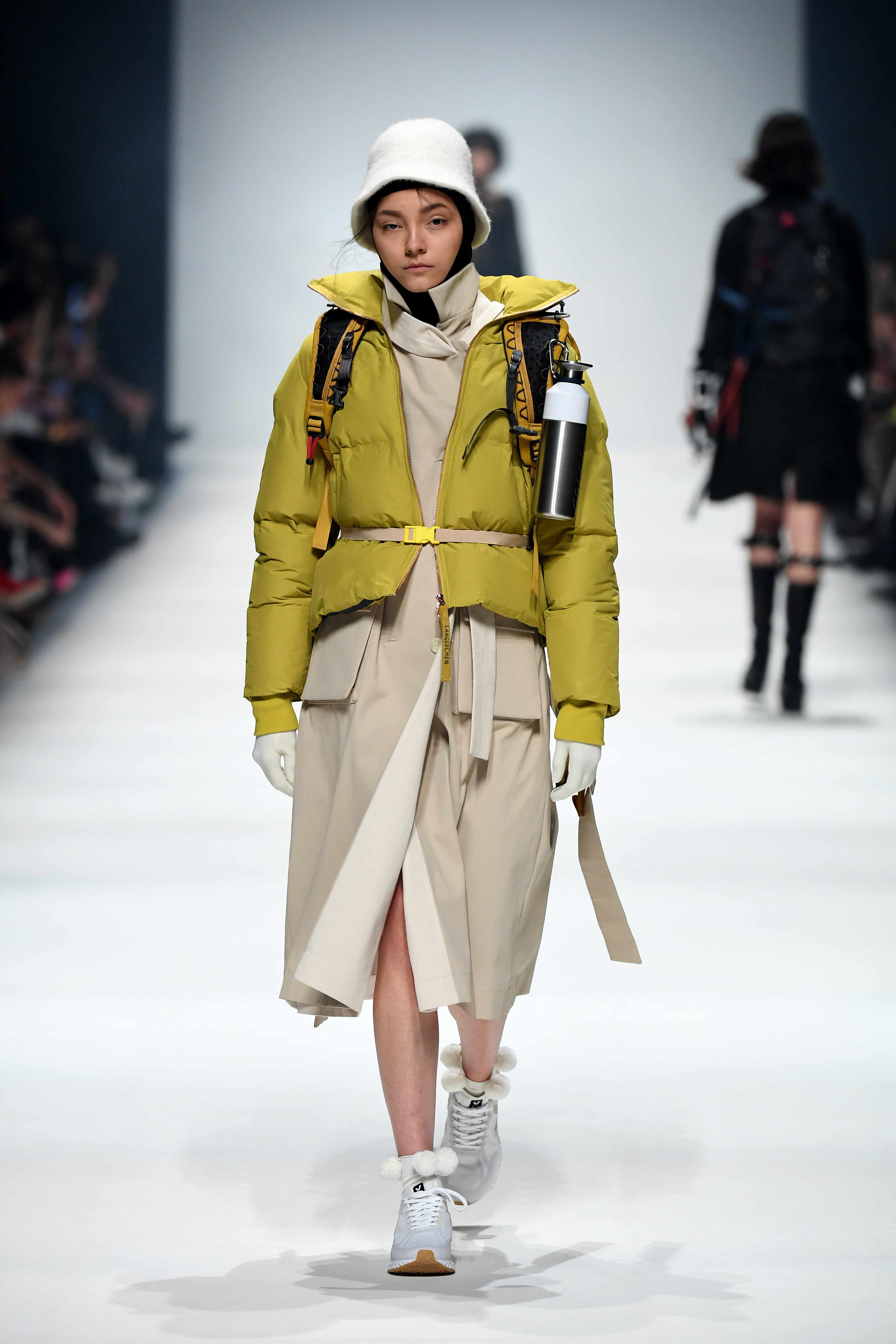 BERLIN, GERMANY - JANUARY 14: A model wearing a jacket by Langer Chen, coat by People Berlin, hood by Falke, hat by Sandermann, socks by Swedish Stockings, belt by People, backpack by Klaettermusen, water bottle by Dopper and shoes by Veja walks the runway at the Neonyt show during Berlin Fashion Week Autumn/Winter 2020 at Kraftwerk Mitte on January 14, 2020 in Berlin, Germany. (Photo by John Phillips/Getty Images for MBFW)