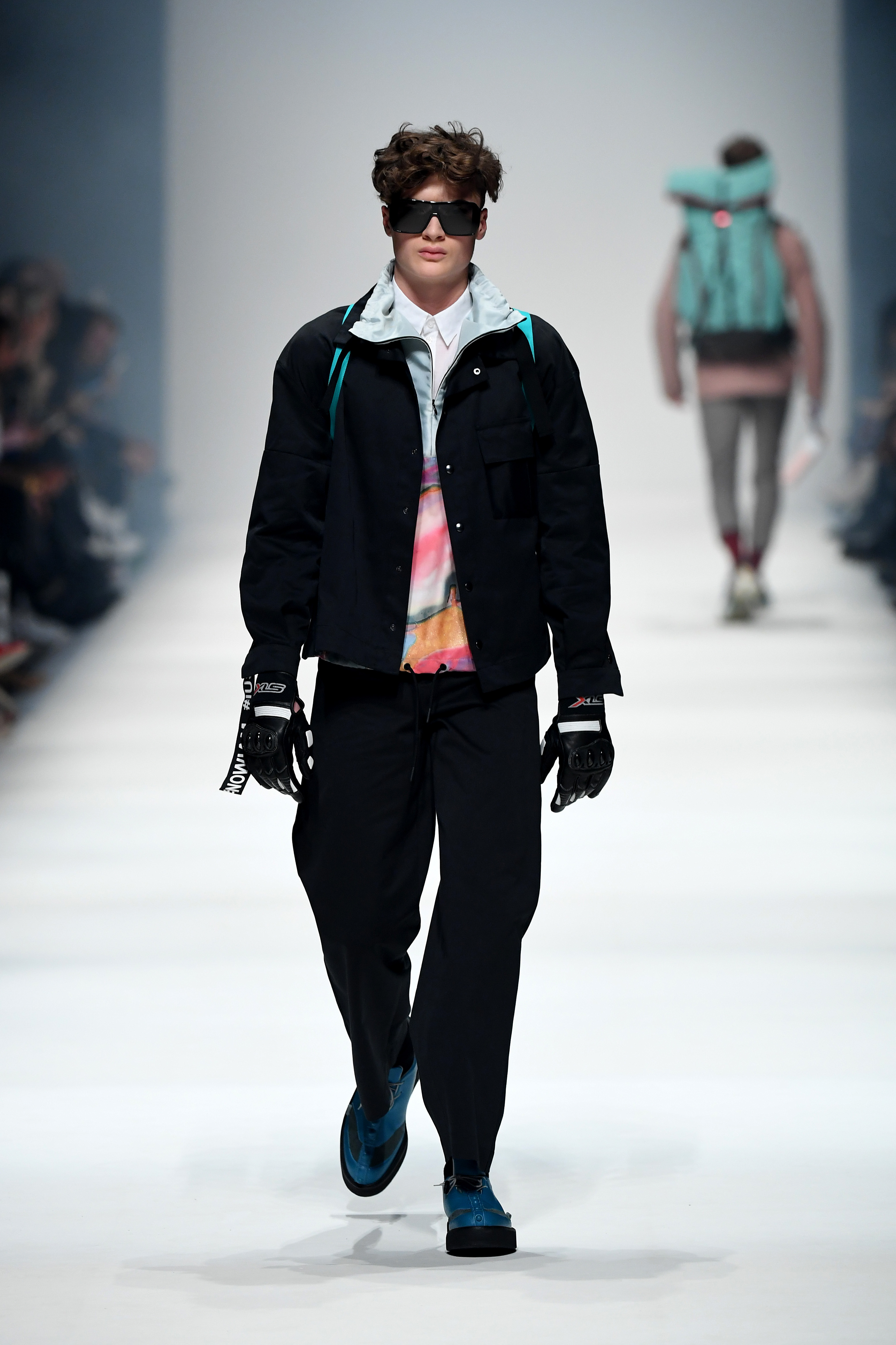 BERLIN, GERMANY - JANUARY 14: A model wearing a suit by AA Gold, zip jacket by Gaya, shirt by Marco Scaiano, bag by Fjaellraeven, glasses by Andy Wolf, gloves by Biker-Zone and shoes by Skua walks the runway at the Neonyt show during Berlin Fashion Week Autumn/Winter 2020 at Kraftwerk Mitte on January 14, 2020 in Berlin, Germany. (Photo by John Phillips/Getty Images for MBFW)