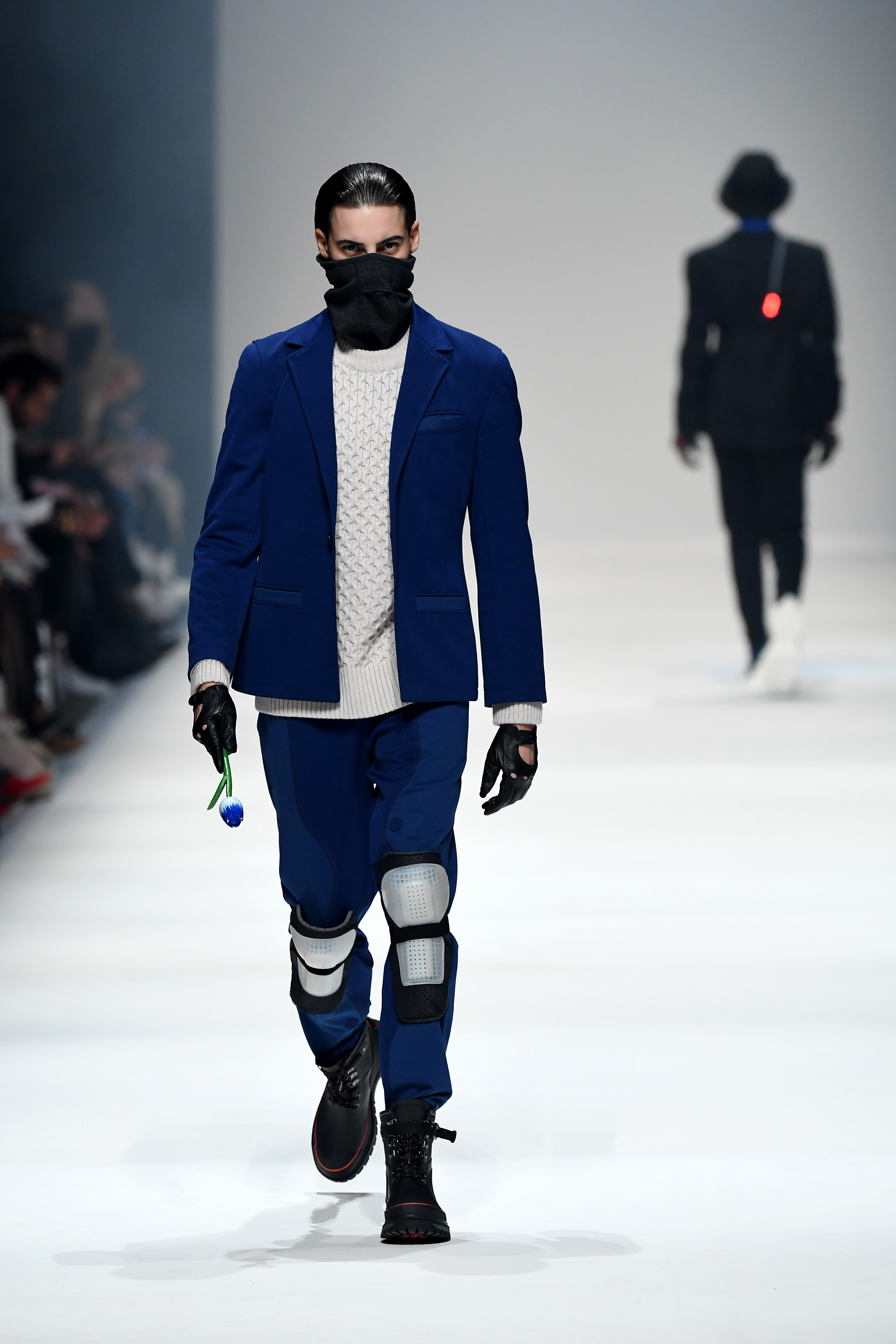 BERLIN, GERMANY - JANUARY 14: A model wearing a suit by Superconductor, pullover by Armedangels, scarf by Icebreaker, gloves by Vintage and shoes by Tretorn X Nigel Cabourn walks the runway at the Neonyt show during Berlin Fashion Week Autumn/Winter 2020 at Kraftwerk Mitte on January 14, 2020 in Berlin, Germany. (Photo by John Phillips/Getty Images for MBFW)