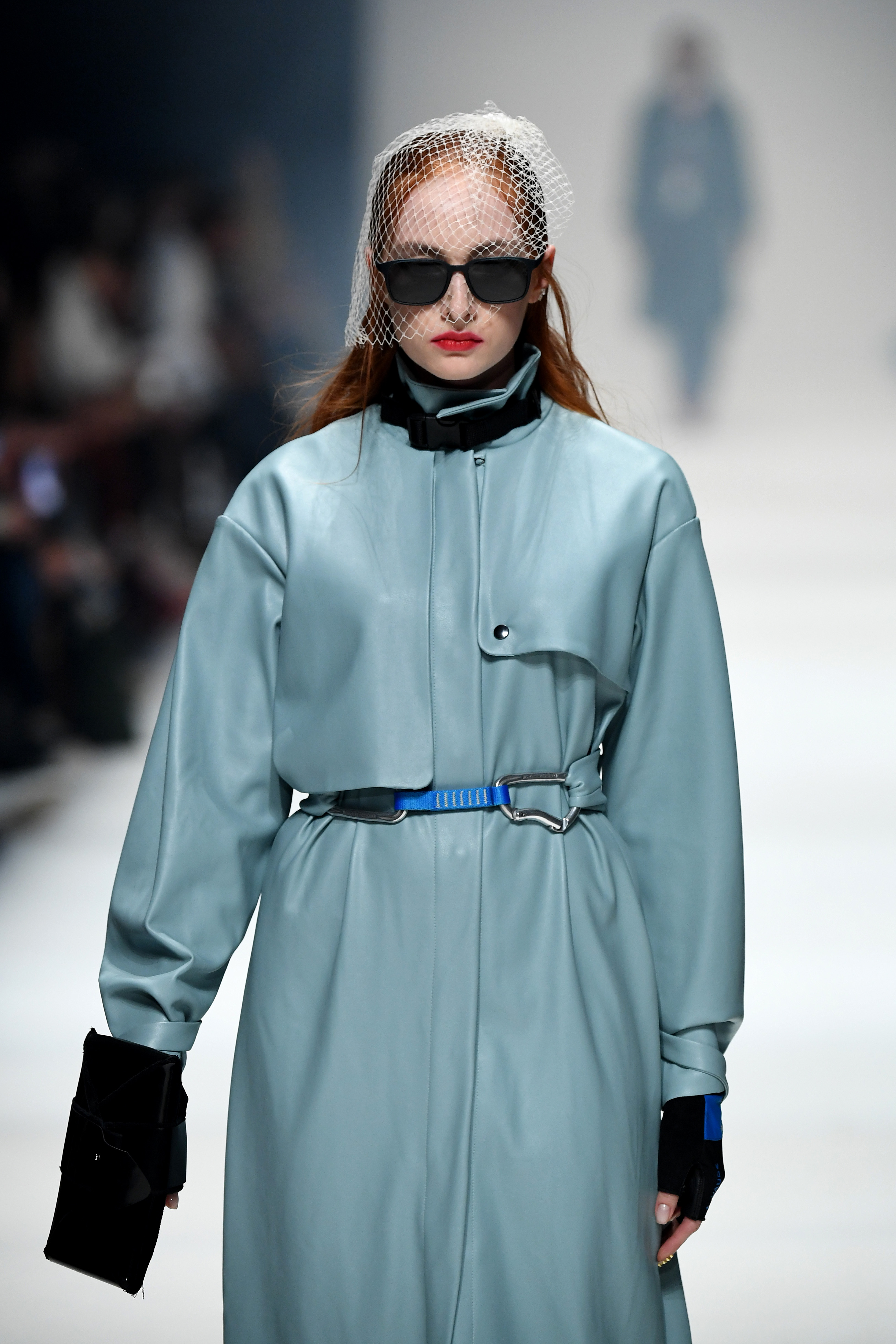 BERLIN, GERMANY - JANUARY 14: A model wearing a coat by Miomartha, headpiece by Spatz Hutdesign, glasses by Neubau Eyewear, gloves by Vaude and a bag by Esther Perbandt walks the runway at the Neonyt show during Berlin Fashion Week Autumn/Winter 2020 at Kraftwerk Mitte on January 14, 2020 in Berlin, Germany. (Photo by John Phillips/Getty Images for MBFW)