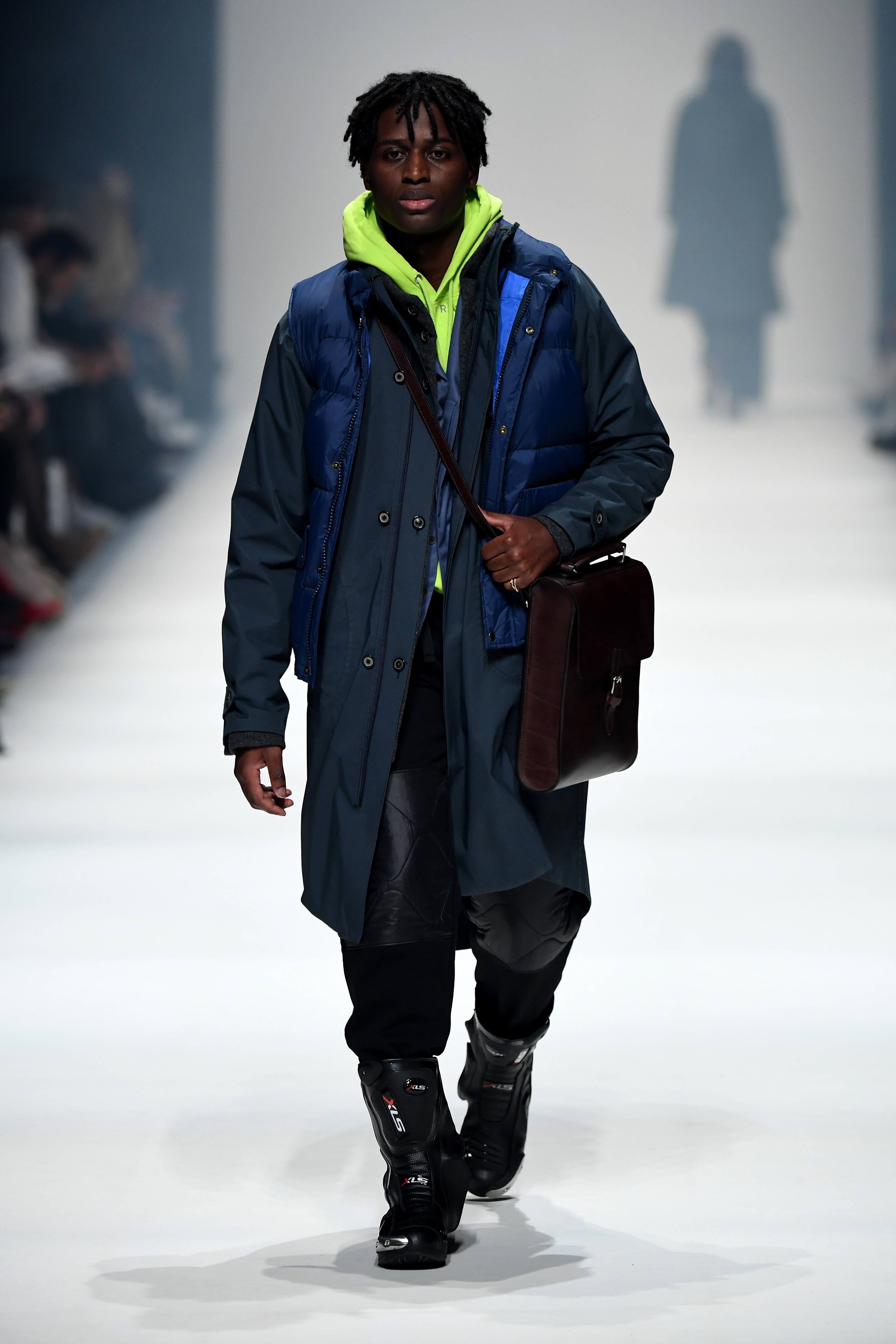 BERLIN, GERMANY - JANUARY 14: A model wearing a coat by Skarabeos, vest by Fjaellraeven, blazer by Brachmann, hoodie by Reer 3, trousers by Timberland, bag by Ackermann, rings by Mies Nobis and shoes by Biker-Zone walks the runway at the Neonyt show during Berlin Fashion Week Autumn/Winter 2020 at Kraftwerk Mitte on January 14, 2020 in Berlin, Germany. (Photo by John Phillips/Getty Images for MBFW)