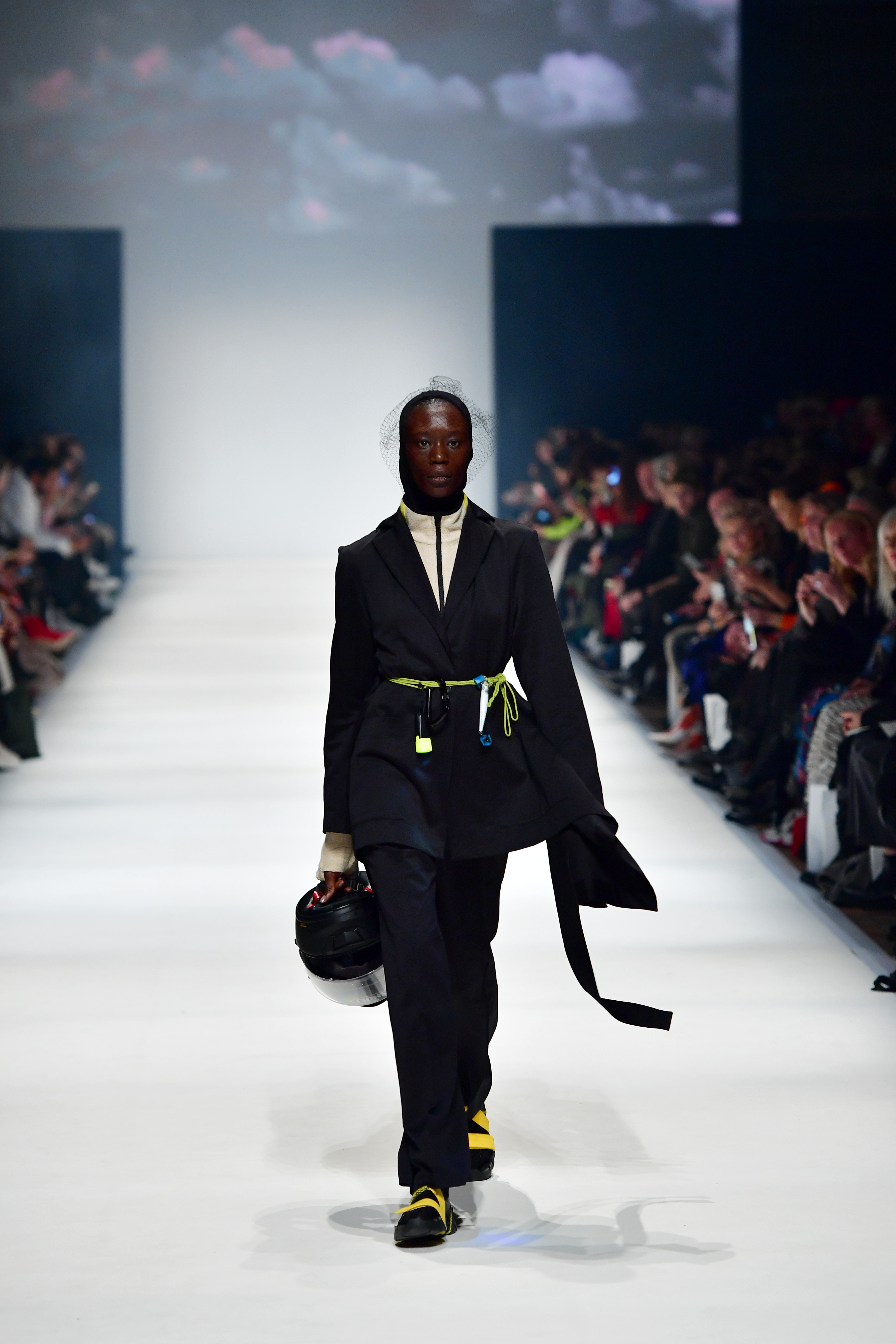 BERLIN, GERMANY - JANUARY 14: A model wearing a suit by Lara Krude, shirt by Hessnatur, hood by Falke, hairnet by Spatz Hutdesign, leg pieces by Trippen, socks by Swedish Stockings and shoe soles by For Ever walks the runway at the Neonyt show during Berlin Fashion Week Autumn/Winter 2020 at Kraftwerk Mitte on January 14, 2020 in Berlin, Germany. (Photo by Alexander Koerner/Getty Images for MBFW)