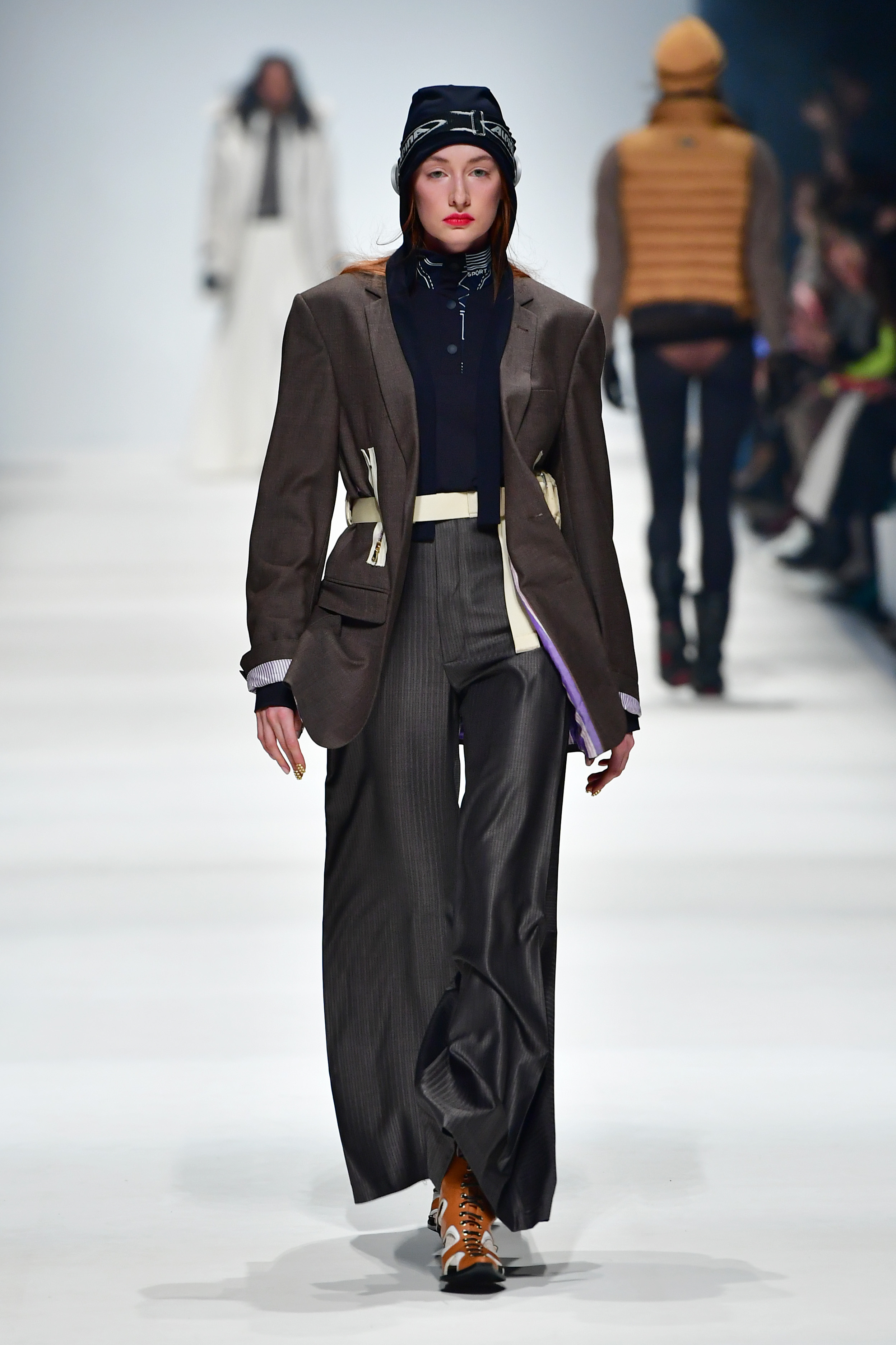 BERLIN, GERMANY - JANUARY 14: A model wearing a blazer by Aftermarch, top by Recto Verso, trousers by Brachmann, hat by Spatz Hutdesign, bag by Wayks, goggles by Stylist's own, socks by Swedish Stockings and shoes by Balluta walks the runway at the Neonyt show during Berlin Fashion Week Autumn/Winter 2020 at Kraftwerk Mitte on January 14, 2020 in Berlin, Germany. (Photo by Alexander Koerner/Getty Images for MBFW)