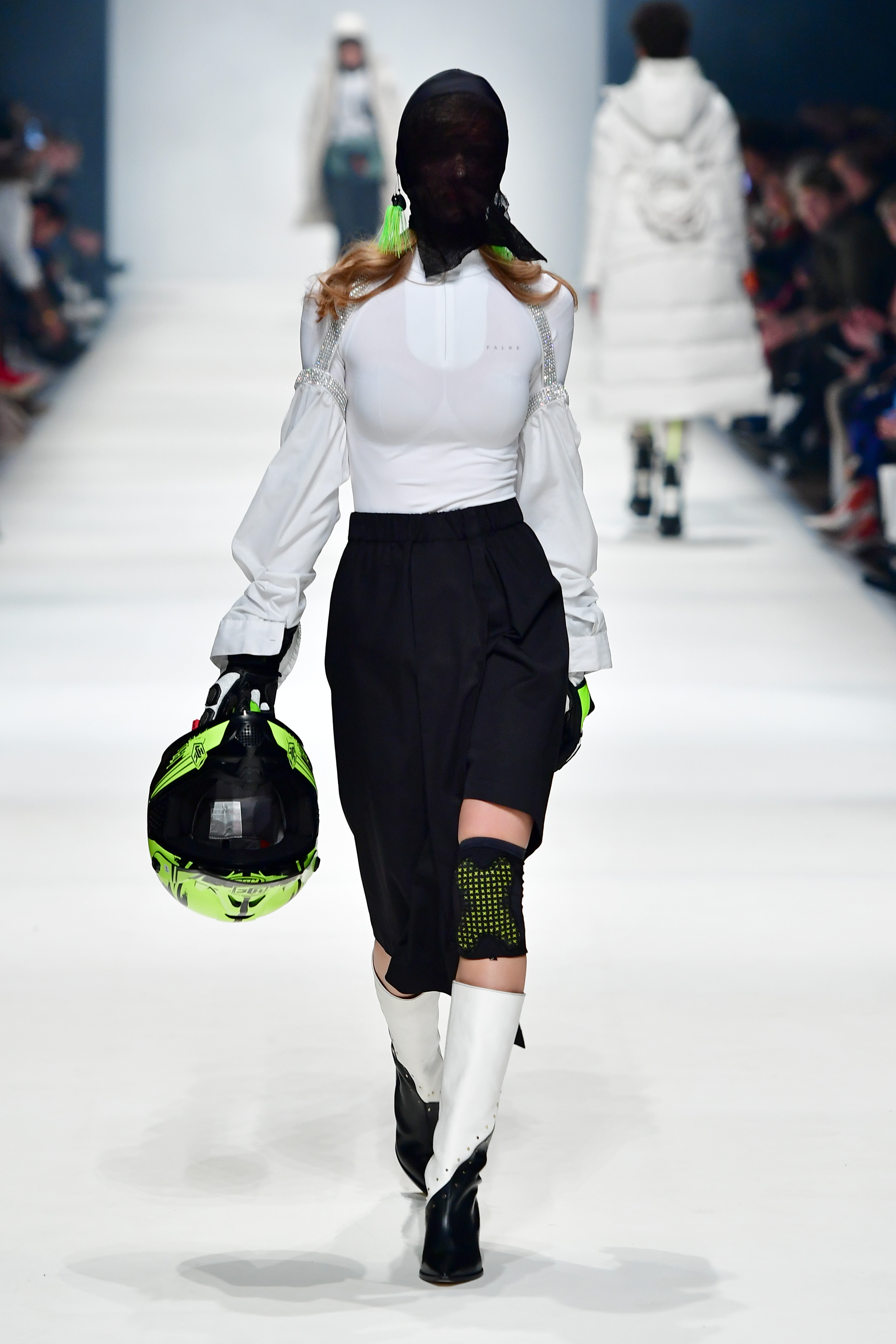 BERLIN, GERMANY - JANUARY 14: A model wearing a top by Falke, sleeves by Lil' Lapel, skirt by Natascha von Hirschhausen, hood & fish hooks by Stylist's own, helmet & gloves by Biker-Zone and shoes by Alinaschuerfeld walks the runway at the Neonyt show during Berlin Fashion Week Autumn/Winter 2020 at Kraftwerk Mitte on January 14, 2020 in Berlin, Germany. (Photo by Alexander Koerner/Getty Images for MBFW)