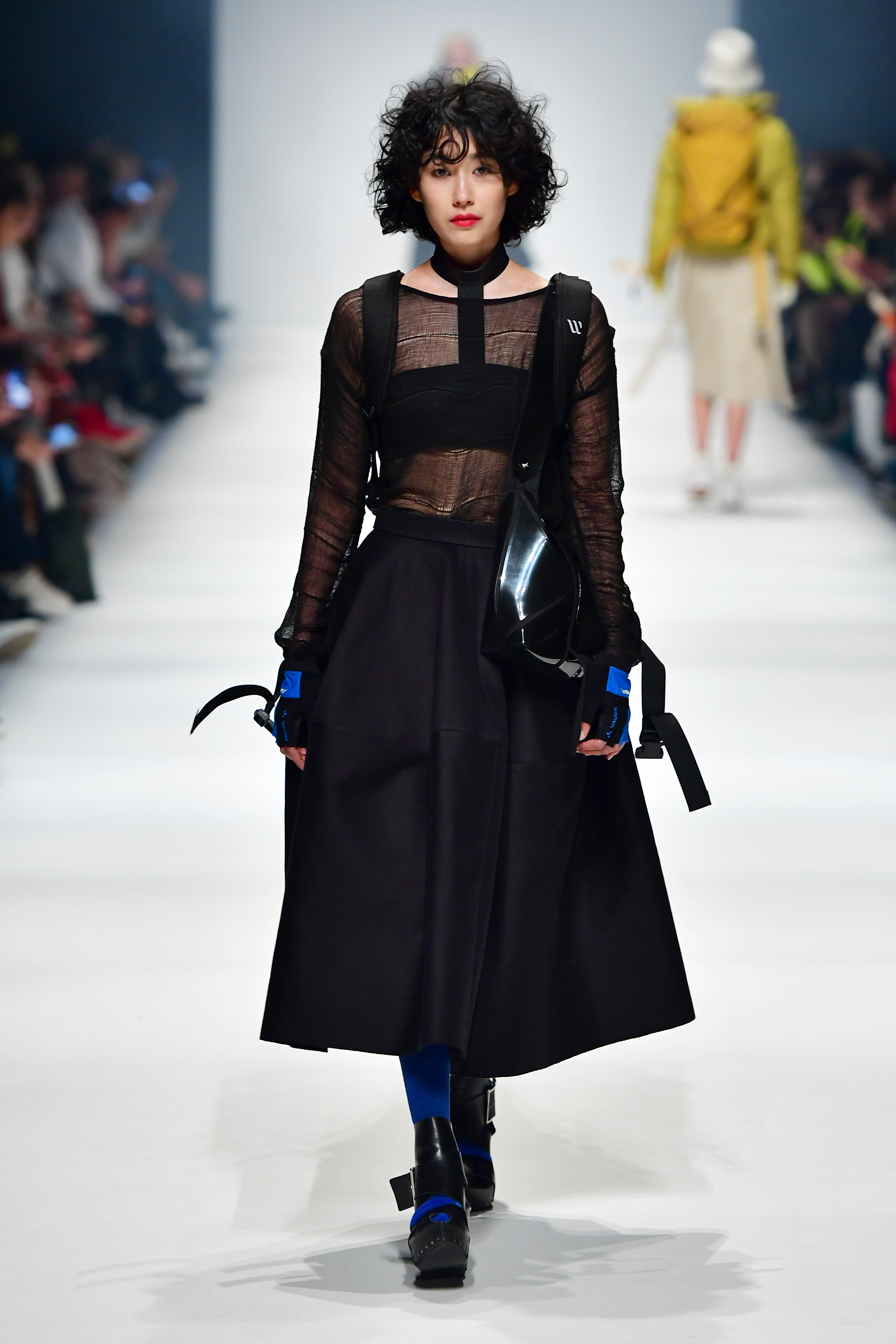 BERLIN, GERMANY - JANUARY 14: A model wearing a top & skirt & bag by Esther Perbandt, bra by Nakt, backpack by Wayks, gloves by Vaude, socks by Falke and shoes by Esther Perbandt X Trippen walks the runway at the Neonyt show during Berlin Fashion Week Autumn/Winter 2020 at Kraftwerk Mitte on January 14, 2020 in Berlin, Germany. (Photo by Alexander Koerner/Getty Images for MBFW)