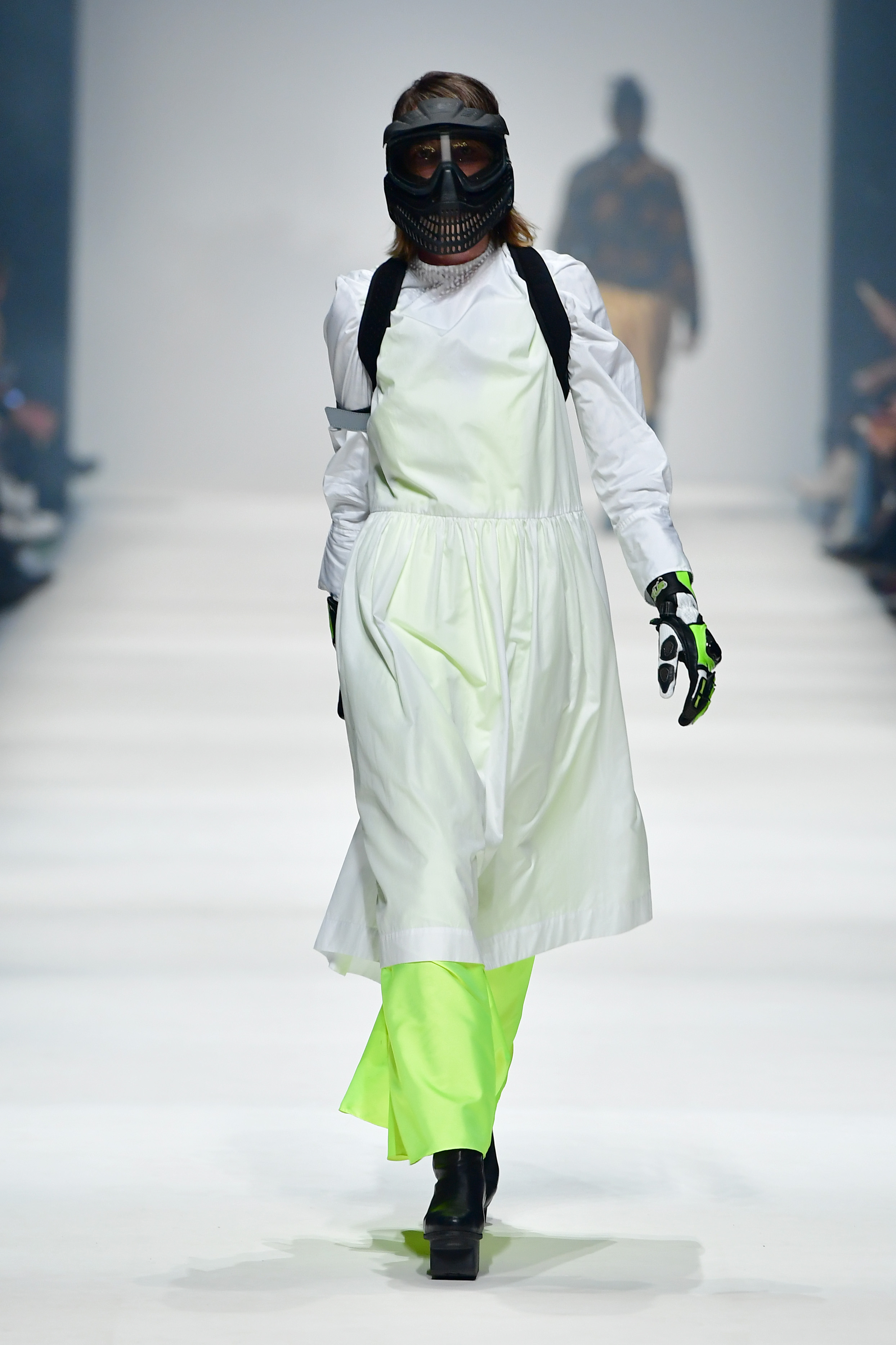 BERLIN, GERMANY - JANUARY 14: A model wearing a white dress by Lara Krude, Neon dress by Maria Roslova, bag by Mimycri, gloves by Biker-Zone and shoes by Trippen walks the runway at the Neonyt show during Berlin Fashion Week Autumn/Winter 2020 at Kraftwerk Mitte on January 14, 2020 in Berlin, Germany. (Photo by Alexander Koerner/Getty Images for MBFW)