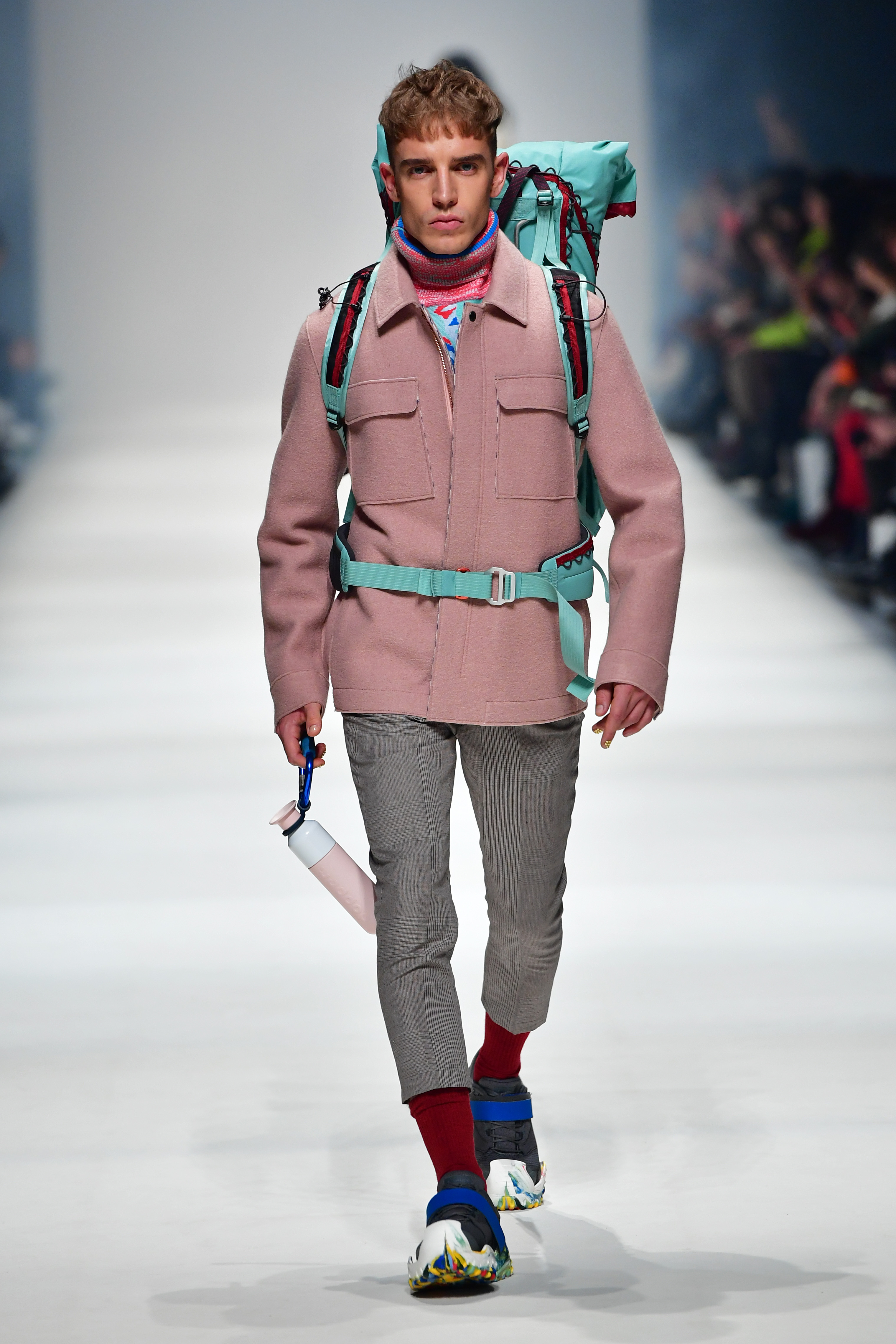 BERLIN, GERMANY - JANUARY 14: A model wearing a jacket by Langer Chen, pullover by Friedrich Dippmann, trousers by Wunderwerk, water bottle by Dopper, backpack by Klaettermusen, shoes by Vaude and shoe soles & straps by For Ever walks the runway at the Neonyt show during Berlin Fashion Week Autumn/Winter 2020 at Kraftwerk Mitte on January 14, 2020 in Berlin, Germany. (Photo by Alexander Koerner/Getty Images for MBFW)