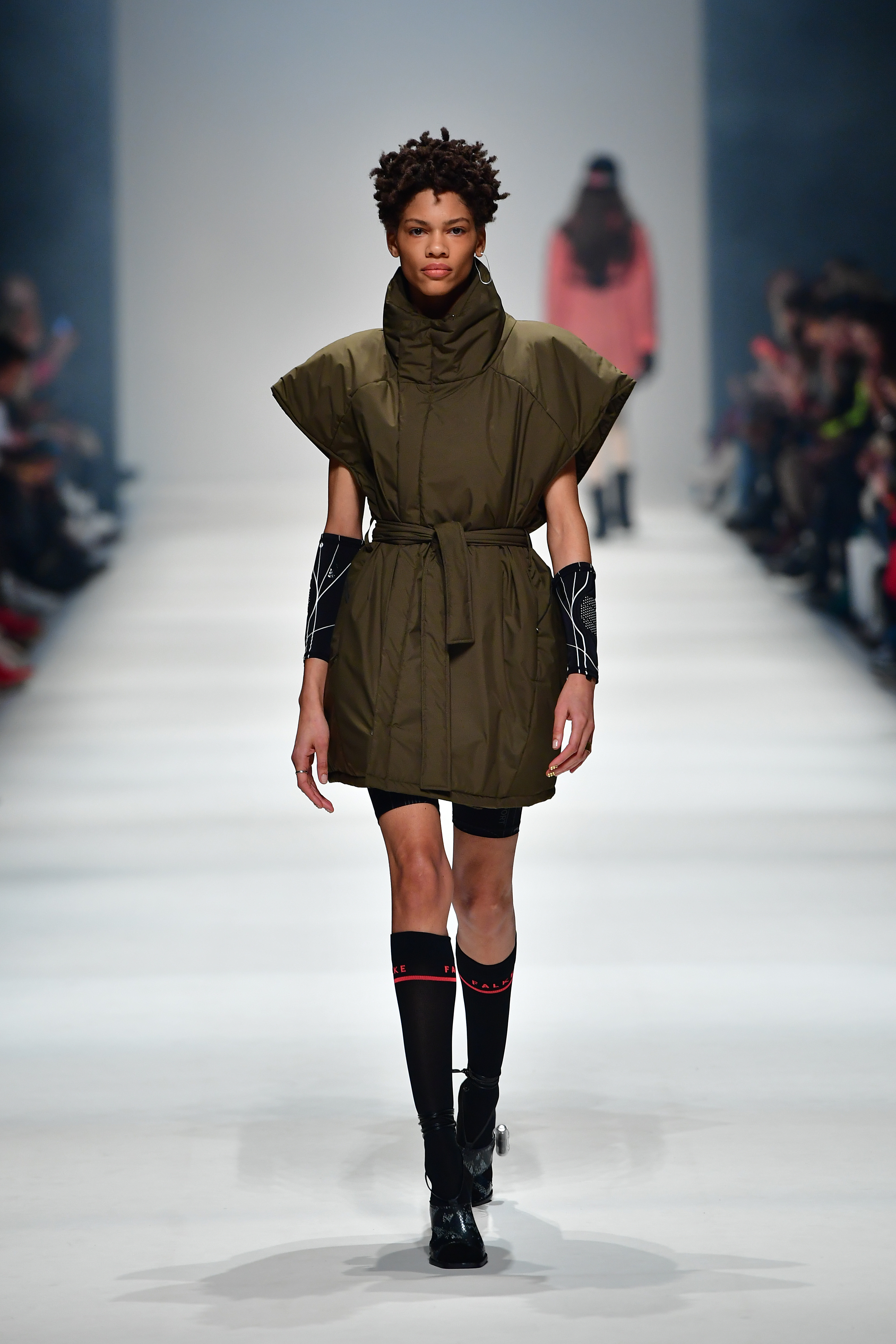 BERLIN, GERMANY - JANUARY 14: A model wearing a vestn by Ayrs, shorts by Recto Verso, earrings by Pulva Jewelry, rings by Folkdays, socks by Falke, shoes by Ballueta walks the runway at the Neonyt show during Berlin Fashion Week Autumn/Winter 2020 at Kraftwerk Mitte on January 14, 2020 in Berlin, Germany. (Photo by Alexander Koerner/Getty Images for MBFW)