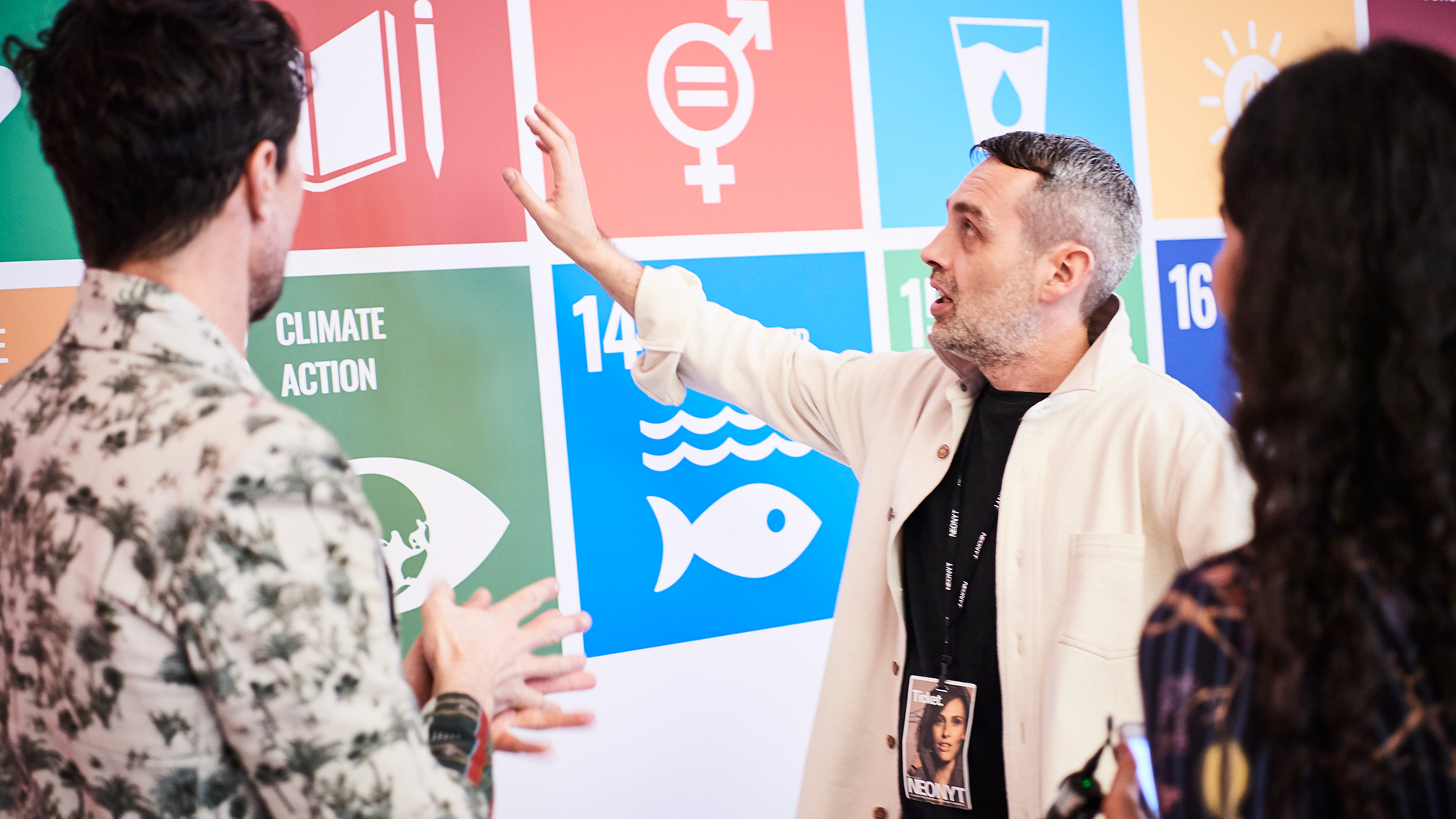 Visitor points to a wall with SDGs at the Neonyt